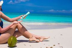 La mujer joven aplica la crema en sus piernas bronceadas lisas en la playa tropical Foto de archivo