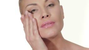 La mujer joven aplica la crema para la cara almacen de metraje de vídeo