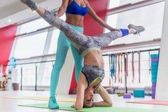 La mujer joven apta que realizaba la pierna del headstand de la yoga partió con la ayuda de un instructor personal en club de dep Fotografía de archivo