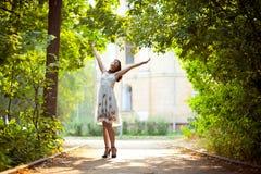 La mujer joven arma levantado gozando del aire fresco adentro Fotografía de archivo