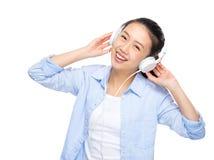 La mujer joven asiática escucha la música con el auricular Foto de archivo