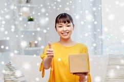 La mujer joven asiática feliz con el paquete encajona en casa Fotos de archivo libres de regalías