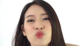 La mujer joven asiática hermosa que se sienta mostrando la llamada video charla hola y gesto del beso alguien en casa almacen de video