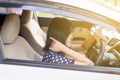 La mujer joven asiática tiene un dolor de cuello mientras que conduce un coche, dando masajes imagen de archivo