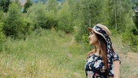 La mujer joven asombrosa en sombrero y vestido del verano da vuelta alrededor ella misma a disfrutar de vacaciones en el campo almacen de video