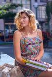 La mujer joven asombrosa, estudiante se está sentando en la calle de la ciudad con Fotos de archivo libres de regalías