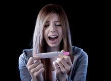 La mujer joven asustó y chocó celebrar el resultado positivo de la prueba de embarazo que parecía infeliz Imágenes de archivo libres de regalías