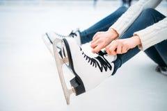 La mujer joven ata los cordones en patines Imágenes de archivo libres de regalías
