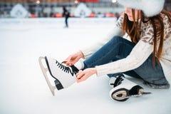 La mujer joven ata los cordones en patines Fotografía de archivo libre de regalías
