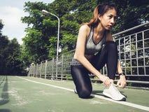 La mujer joven ata para arriba su zapato listo al entrenamiento en el ejercicio en el parque con sol ligera caliente por mañana Foto de archivo libre de regalías