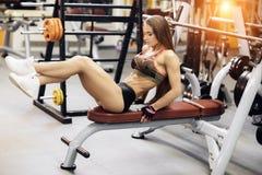 La mujer joven atlética ejercita para el ABS en la prensa de banco fotos de archivo