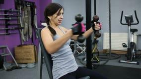 La mujer joven atlética se ocupa de pesas de gimnasia en el gimnasio metrajes