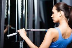 La mujer joven atlética se resuelve en el entrenamiento de la gimnasia Fotografía de archivo libre de regalías