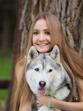La mujer joven atractiva abraza el perro divertido del husky siberiano con los ojos marrones que muestran su lengua Imagenes de archivo