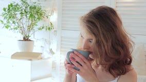 La mujer joven atractiva bebe cuidadosamente el café de una taza por la mañana almacen de metraje de vídeo