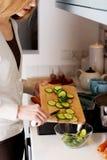 La mujer joven atractiva caucásica está cortando el pepino. Fotografía de archivo