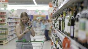 La mujer joven atractiva con el carro de la compra elige el vino en una tienda de la botella que se coloca delante de estantes po almacen de video