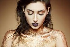La mujer joven atractiva con el fashon compone con brillo del oro encendido imagen de archivo