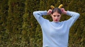La mujer joven atractiva con los labios rojos en suéter azul pone plátanos a su cabeza como cuernos e imita el imp angelical