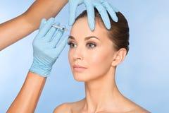 La mujer joven atractiva consigue la inyección cosmética del botox foto de archivo