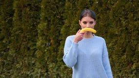 La mujer joven atractiva del retrato con el pelo oscuro y los labios rojos en chaqueta azul saca el plátano y lo aplica que imita