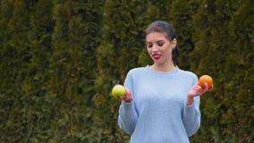 La mujer joven atractiva del retrato en chaqueta azul elige entre la manzana verde y la naranja dulce, decide morder la manzana
