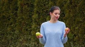 La mujer joven atractiva del retrato en chaqueta azul elige entre la manzana verde y la manzana roja, decide morder la manzana ve