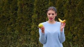La mujer joven atractiva del retrato en chaqueta azul elige entre la manzana y el plátano verdes