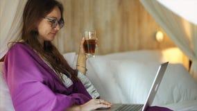 La mujer joven atractiva en albornoz est? charlando en Internet almacen de metraje de vídeo