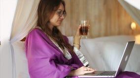 La mujer joven atractiva en albornoz est? charlando en Internet almacen de video