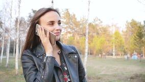 La mujer joven atractiva en el parque utiliza el tel?fono paseo a trav?s del centro de ciudad por la tarde Una mujer joven camina almacen de metraje de vídeo