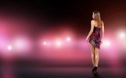 La mujer joven atractiva en el vestido de la colocación rodeado por el cuidado y la cámara destellan Celebridad, modelo, estrella fotos de archivo libres de regalías