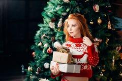 La mujer joven atractiva en suéter se está preparando para celebrar Año Nuevo en casa Foto de archivo