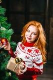 La mujer joven atractiva en suéter se está preparando para celebrar Año Nuevo en casa Fotos de archivo libres de regalías