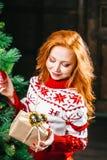 La mujer joven atractiva en suéter se está preparando para celebrar Año Nuevo en casa Foto de archivo libre de regalías