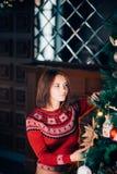 La mujer joven atractiva en suéteres se está preparando para celebrar Año Nuevo en casa Imágenes de archivo libres de regalías
