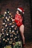La mujer joven atractiva en suéteres se está preparando para celebrar Año Nuevo en casa Imagen de archivo