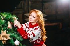 La mujer joven atractiva en suéteres se está preparando para celebrar Año Nuevo en casa Fotografía de archivo libre de regalías