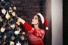 La mujer joven atractiva en suéteres se está preparando para celebrar Año Nuevo en casa Imagen de archivo libre de regalías