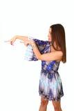 La mujer joven atractiva en una alineada azul señala a la izquierda Fotos de archivo libres de regalías