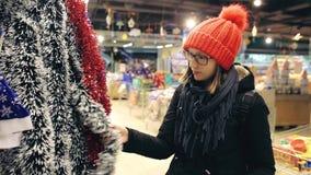La mujer joven atractiva en vidrios y sombrero rojo elige la decoración de la Navidad para un árbol de navidad El comprador encon metrajes