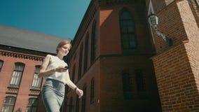 La mujer joven atractiva está utilizando el smartphone app durante paseo afuera en 4k metrajes