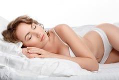 La mujer joven atractiva está durmiendo en su cama Muchacha en ropa interior en Foto de archivo