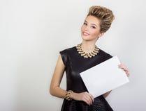 La mujer joven atractiva feliz hermosa que sonríe en un vestido de noche negro con el pelo y el maquillaje con joyería un blanco  Fotografía de archivo