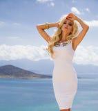 La mujer joven atractiva hermosa del pelo largo rizado rubio se está colocando en el vestido costoso atractivo desafiador blanco  Fotos de archivo