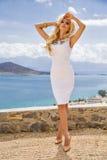 La mujer joven atractiva hermosa del pelo largo rizado rubio se está colocando en el vestido costoso atractivo desafiador blanco  Imagen de archivo libre de regalías