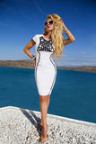 La mujer joven atractiva hermosa del pelo largo rizado rubio se está colocando en el vestido costoso atractivo desafiador blanco  Fotografía de archivo