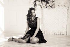 La mujer joven atractiva hermosa en vestido negro se está sentando en el piso Mujer elegante joven en alineada negra foto de archivo libre de regalías