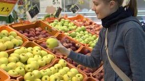 La mujer joven atractiva hermosa que escoge manzanas da fruto en supermercado Concepto sano de la consumición almacen de metraje de vídeo