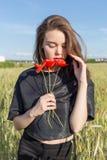 La mujer joven atractiva linda hermosa con los labios llenos con el pelo corto en un campo con la amapola florece en sus manos Fotografía de archivo